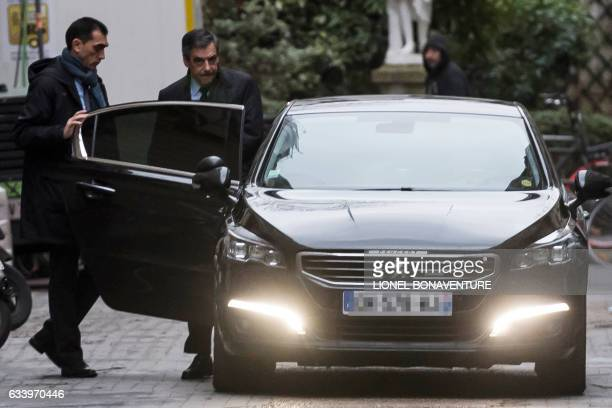 TOPSHOT French presidential election candidate for the rightwing Les Republicains party Francois Fillon steps in a car as he leaves his home to his...