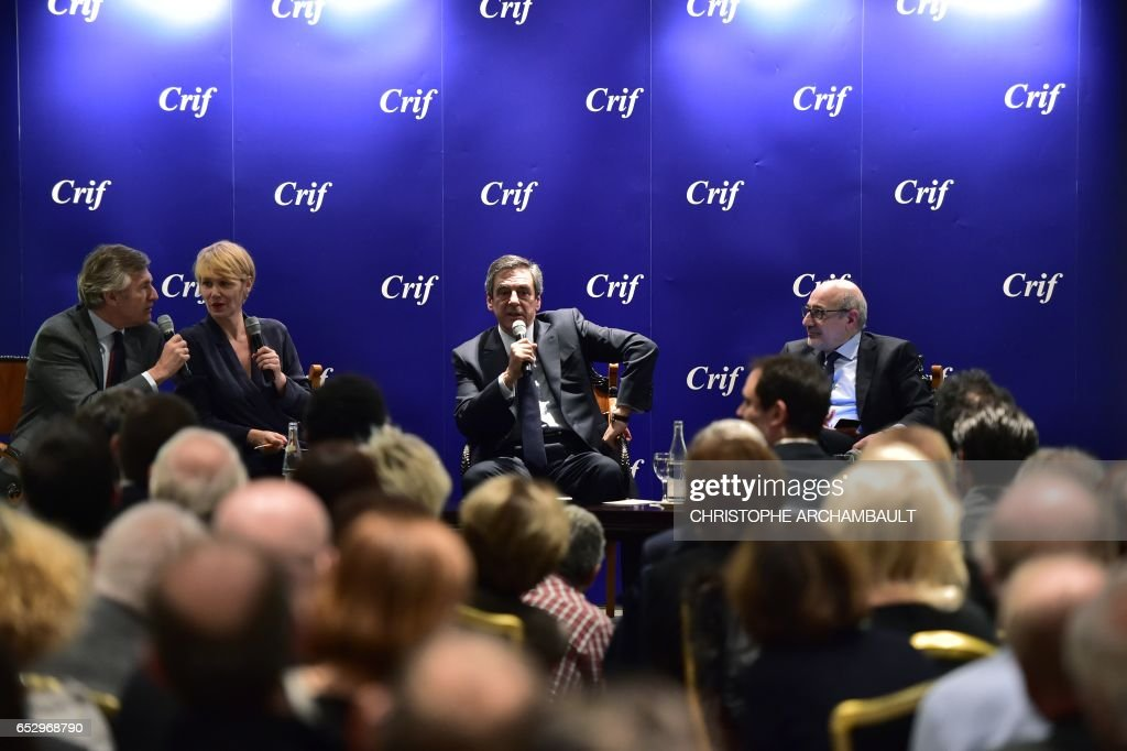 French presidential election candidate for the right-wing Les Republicains (LR) party Francois Fillon (C), flanked by Francis Kalifat (R) president of the Jewish Institutions Representative Council (Conseil Representatif des Institutions juives de France - CRIF) and TV hosts, speaks during a conference CRIF on March 13, 2017 in Paris. /
