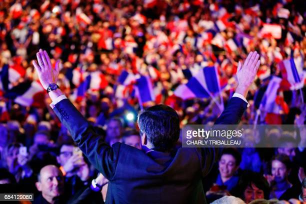 TOPSHOT French presidential election candidate for the rightwing Les Republicains party Francois Fillon waves as he arrives for a campaign rally on...