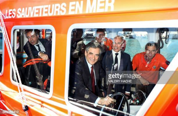 French presidential election candidate for the rightwing Les Republicains party Francois Fillon holds the helm of a rescue boat next to president of...