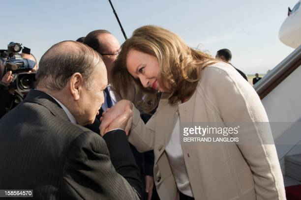 French President's companion Valerie Trierweiler is welcomed by Algerian president Abdelaziz Bouteflika at the airport in Algiers on December 19 2012...