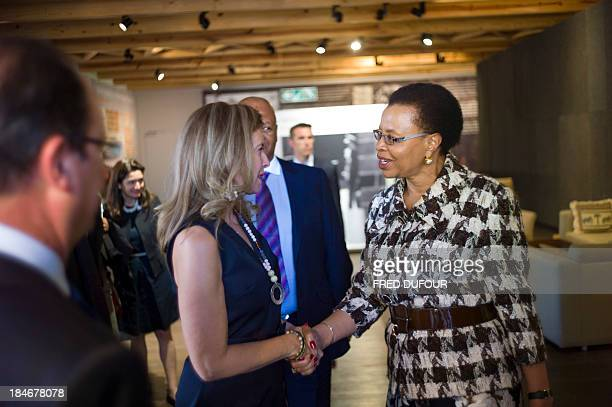 French President's companion Valerie Trierweiler shakes hands with Nelson Mandela's wife Graca Machel during a visit to the Mandela foundation on...