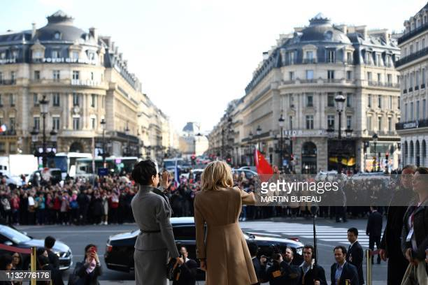 French president's wife Brigitte Macron and Chinese president's wife Peng Liyuan wave to a crowd as they visit the Palais Garnier opera house in...