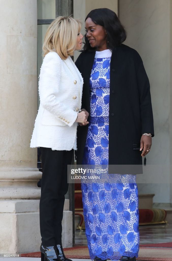 French President's wife Brigitte Macron (L) embraces Liberian President's wife Clar Duncan Weah as she departs from The Elysee Palace in Paris on February 21, 2018, after attending a lunch function. /