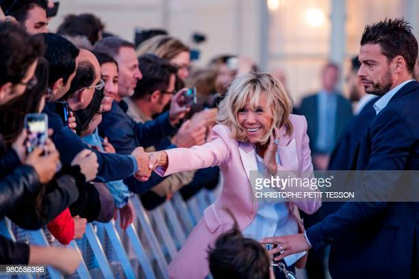 French president's wife Brigitte Macron greets people during the annual 'Fete de la Musique' in the courtyard of the Elysee Palace in Paris on June...