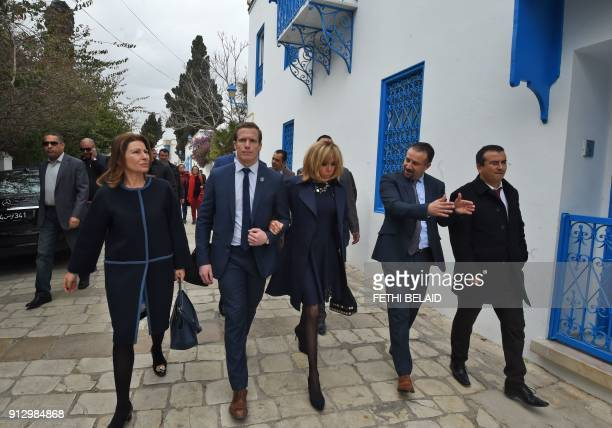 French president's wife Brigitte Macron is escorted by a members of her personnel security detail during a visit to the town of Sidi Bou Said near...