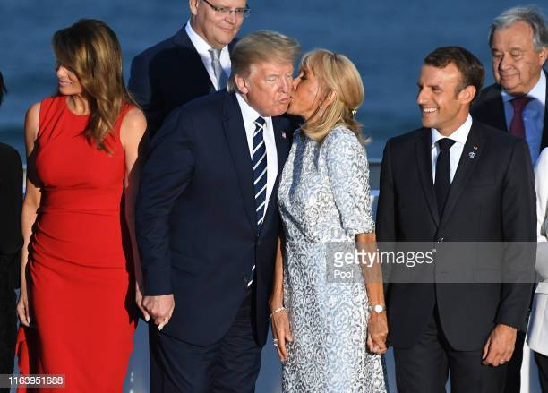French President's wife Brigitte Macron kisses US President Donald Trump as G7 leaders and guests gather for a family picture in front of the...