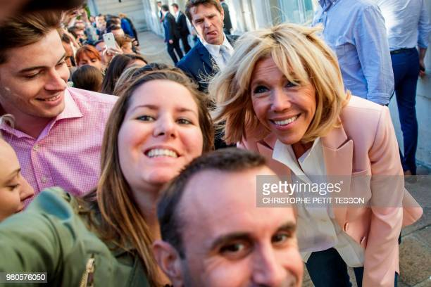 French president's wife Brigitte Macron poses for pictures during the annual 'Fete de la Musique' in the courtyard of the Elysee Palace in Paris on...
