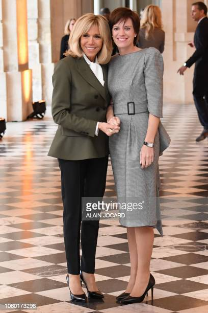 French President's wife Brigitte Macron poses with Belgian Prime Minister's partner Amelie Derbaudrenghien as they take part in a spousal event at...