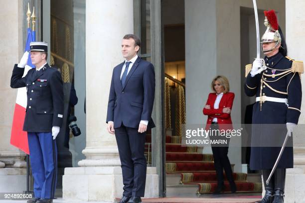 French President's wife Brigitte Macron stands behind her husband Emmanuel Macron as he waits for guest at the entrance of the Elysee presidential...