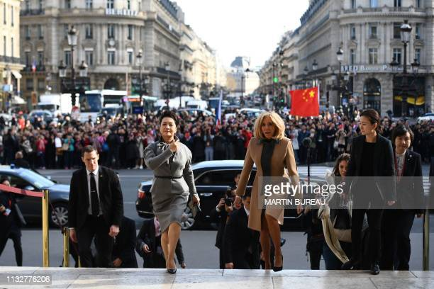 French president's wife Brigitte Macron walks with Chinese president's wife Peng Liyuan as they visit the Palais Garnier opera house in Paris on...