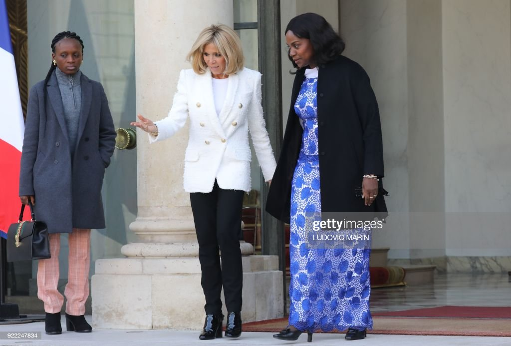 French President's wife Brigitte Macron (2L) walks with Liberian President's wife Clar Duncan Weah (R) as she departs from The Elysee Palace in Paris on February 21, 2018, after attending a lunch function. /