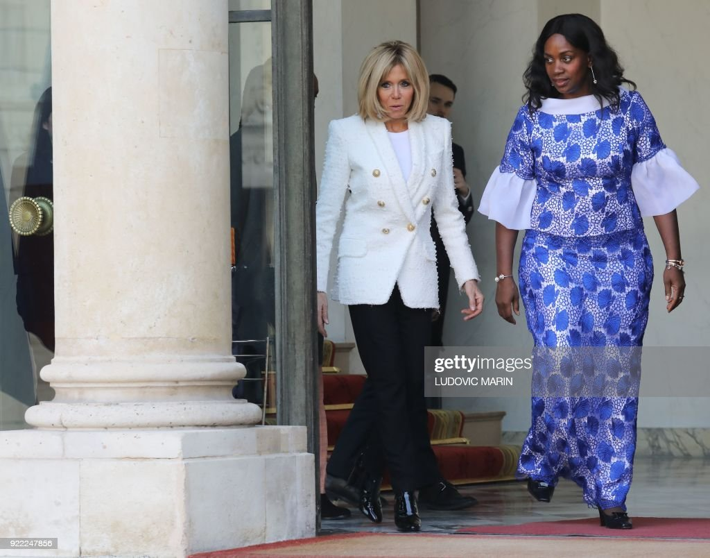 French President's wife Brigitte Macron (C) walks with Liberian President's wife Clar Duncan Weah (R) as she departs from The Elysee Palace in Paris on February 21, 2018, after attending a lunch function. /