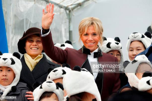 French president's wife Brigitte Macron waves as she poses with children dressed in panda outfits during a naming ceremony for a male panda born at...