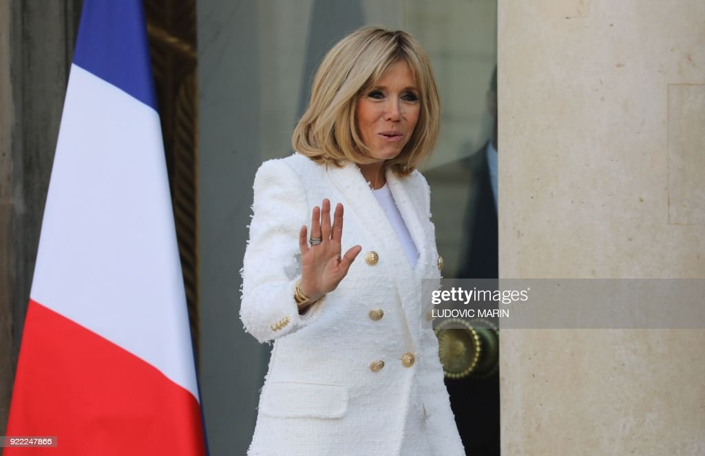 French President's wife Brigitte Macron waves to media representatives as Liberian President's wife Clar Duncan Weah departed from The Elysee Palace in Paris on February 21, 2018, after attending a lunch function. /