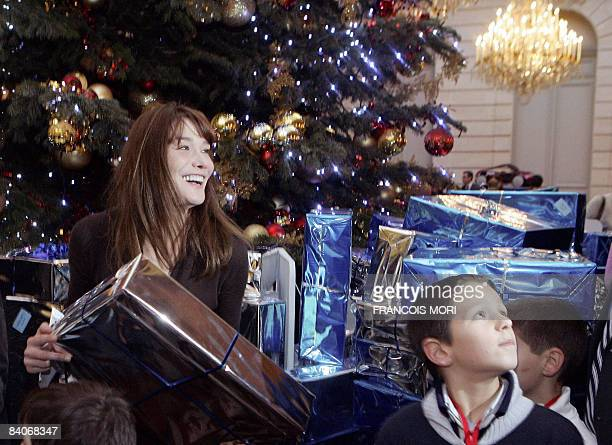 French President's wife Carla BruniSarkozy offers gifts to children during the traditional Christmas party at the Elysee Palace on December 17 2008...