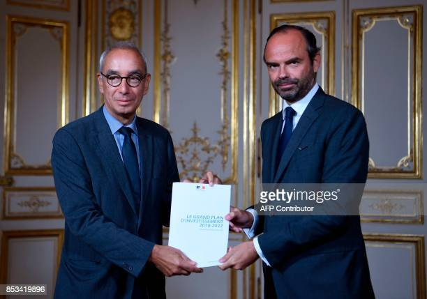 French Prime Minister Edouard Philippe and French economist Jean PisaniFerry pose with a report by PisaniFerry on France's Grand Investment Plan for...