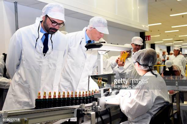 French Prime Minister Edouard Philippe and French Economy Minister Bruno Le Maire look at an employee working on lipsticks during a visit of the...
