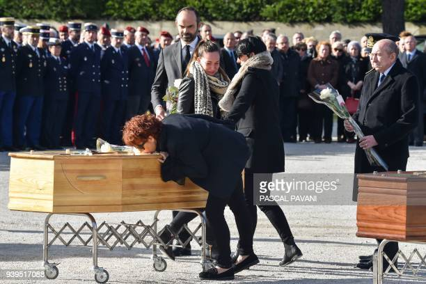 French Prime Minister Edouard Philippe and French Interior Minister Gerard Collomb stands by as family members pay their last respects during the...