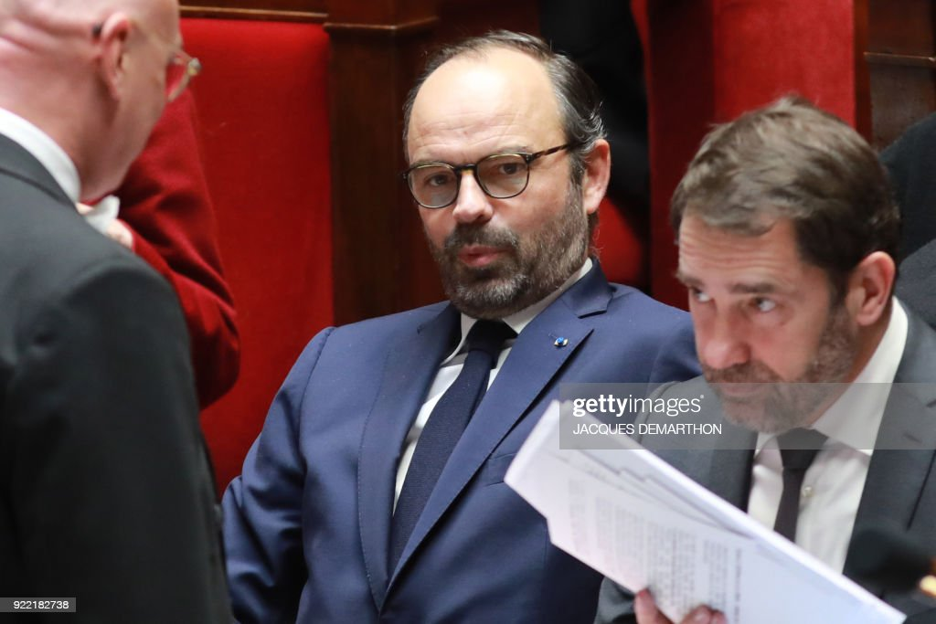French Prime Minister Edouard Philippe (C) and French Junior Minister for the Relations with Parliament Christophe Castaner (R) attend a session of questions to the government at the National Assembly in Paris on February 21, 2018. /