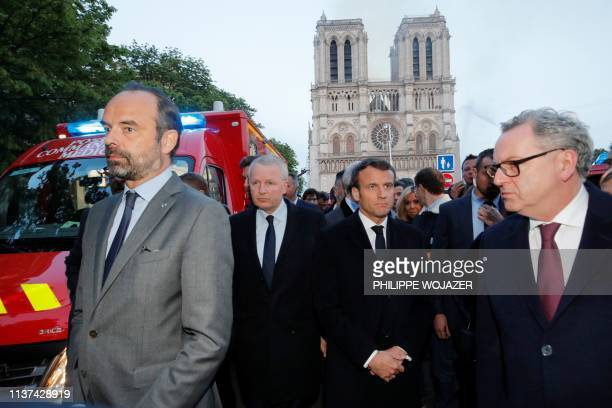 TOPSHOT French Prime Minister Edouard Philippe and French President Emmanuel Macron gather in near the entrance of the NotreDame de Paris Cathedral...
