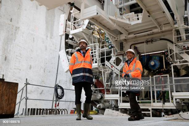 French Prime Minister Edouard Philippe and French Transports Minister Elisabeth Borne stand by a tunnel boring machine as they visit the drilling...