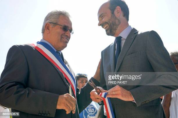 French Prime Minister Edouard Philippe and MontDore mayor Eric Gay react after cutting the ribbon during the inauguration of a high school on...