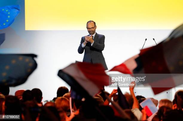 French Prime Minister Edouard Philippe applauds the audience during a meeting of the La Republique en Marche political party in Paris on July 8 2017...