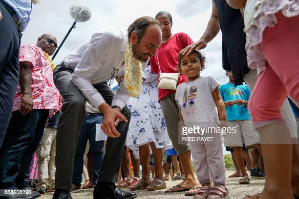 French Prime Minister Edouard Philippe bends down to greet a small girl in the town of We on Lifou Island on December 3 during his visit to the...