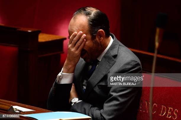 French Prime Minister Edouard Philippe covers his face with his hand as he attends a session of questions to the government at the National Assembly...