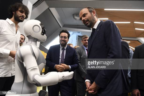 French Prime Minister Edouard Philippe flanked by French Junior Minister for the Digital Sector Mounir Mahjoubi speaks with a robot as they visit the...