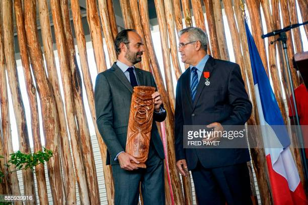 French Prime Minister Edouard Philippe holding a traditional wood carving talks with MontDore mayor Eric Gay during a decoration ceremony for Gay...