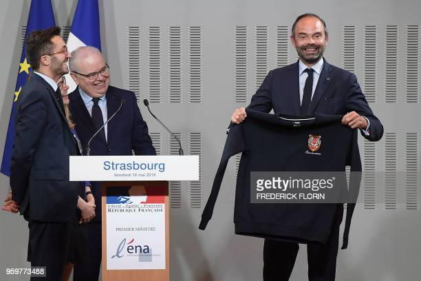 """French Prime Minister Edouard Philippe holds a sweater of ENA's 2017-18 promotion """"Clemenceau"""" he was offered by ENA's director Patrick Gerard after..."""