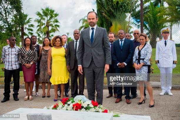 French Prime Minister Edouard Philippe lays a wreath of flowers on the tomb of French poet Aime Cesaire at De La Joyau cemetery flanked by prefect...