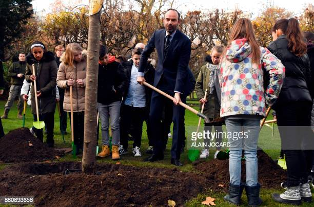 French Prime Minister Edouard Philippe plants an apple tree with pupils from the primary school of Theophile Gautier in le Havre in the garden of the...
