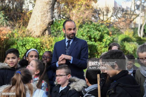 French Prime Minister Edouard Philippe prepares to plant an apple tree with pupils from the primary school of Theophile Gautier in le Havre in the...