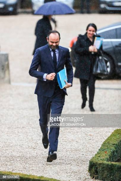 French Prime Minister Edouard Philippe runs to avoid getting wet in the rain as he arrives to attend a session of questions to the government at the...