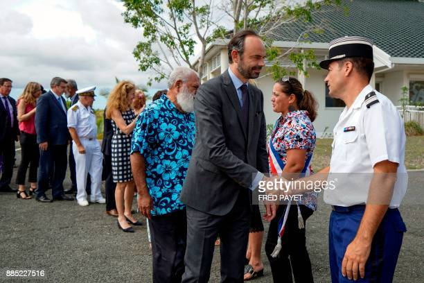 French Prime Minister Edouard Philippe shakes hands with a gendarme as he arrives for a welcoming ceremony arrives to visit Kone a city in Grande...