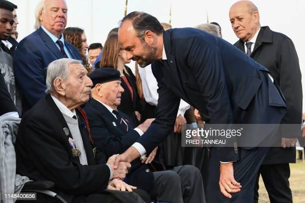 French Prime Minister Edouard Philippe shakes hands with an army veteran during an international ceremony on Juno Beach in Courseulles-sur-Mer,...