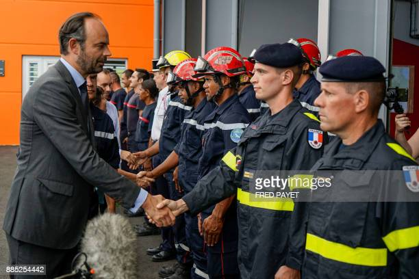 French Prime Minister Edouard Philippe shakes hands with firemen during the inauguration of the KonePouembout rescue centre in Kone a city in Grande...