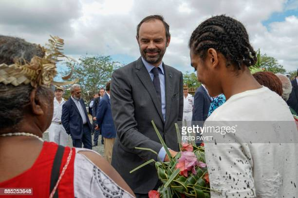 French Prime Minister Edouard Philippe shakes hands with inhabitants as he visits an activity zone in the customary area of Kone a city in Grande...