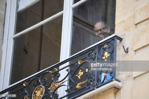 French Prime Minister Edouard Philippe smiles looking from a window at the Hotel de Matignon on April 25 2018 in Paris after a meeting with the...