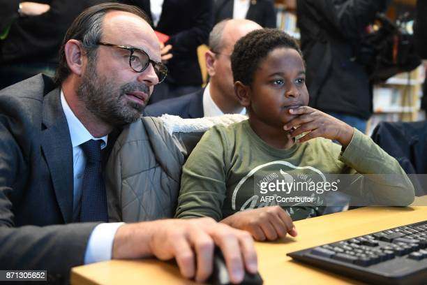 French Prime Minister Edouard Philippe speaks with a pupil as he visits the Jean Perrin secondary school in Nanterre outside Paris on November 7 2017...
