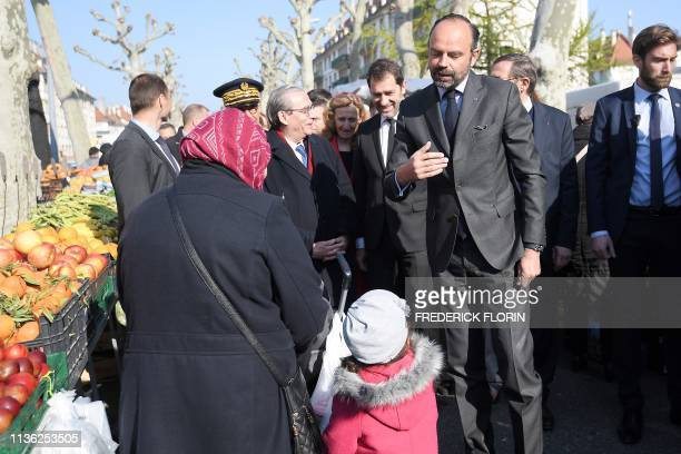 French Prime Minister Edouard Philippe speaks with a woman and a child as he visits a market with Mayor of Strasbourg Roland Ries ahead of the...