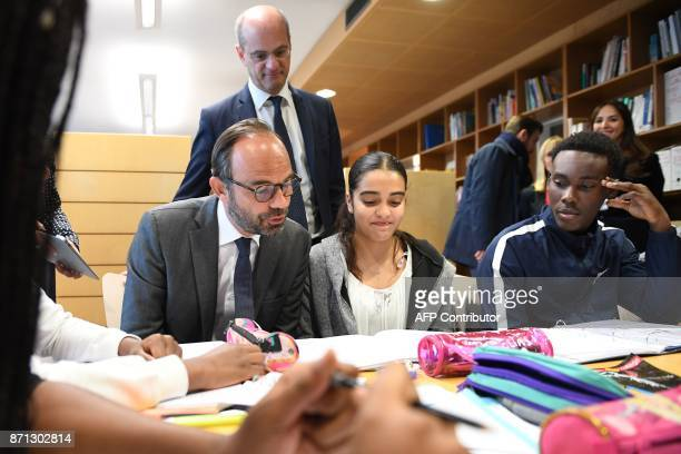 French Prime Minister Edouard Philippe speaks with pupils as he visits the Jean Perrin secondary school flanked by French Education Minister...