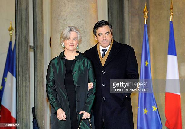 French Prime minister Francois Fillon and his wife Penelope pose as they arrive at the Elysee Palace to take part in an official dinner with French...