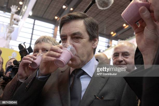 French Prime Minister Francois Fillon drinks a glass of milk on February 23 2009 as he visits the 46th International Agricultural Fair in Paris Part...