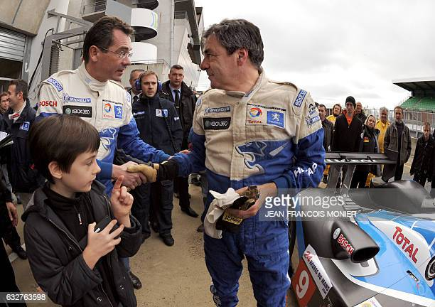 French Prime Minister Francois Fillon is congratulated by JeanMarc Gales General Peugeot Citroën's director after driving the Peugeot 908 HDI FAP N°...