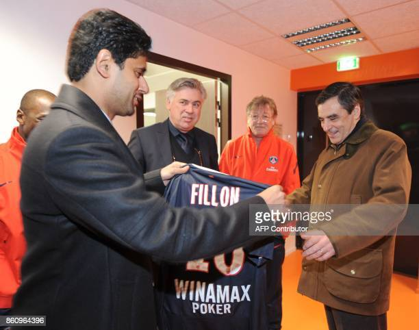 French Prime Minister Francois Fillon is offered a football jersey with his name by Paris SaintGermains Qatar President and CEO Nasser Al Khelaifi as...