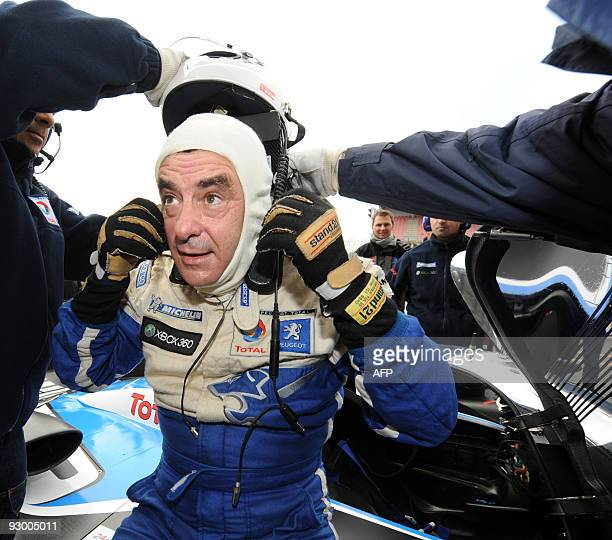 French Prime Minister Francois Fillon puts his helmet of after driving the Peugeot 908 HDI FAP N° 9 the winning car of the 2009 edition of Le Mans'...